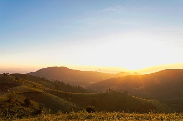 Schöner landschaftssonnenaufgang über den bergen mit ländlichem hintergrund