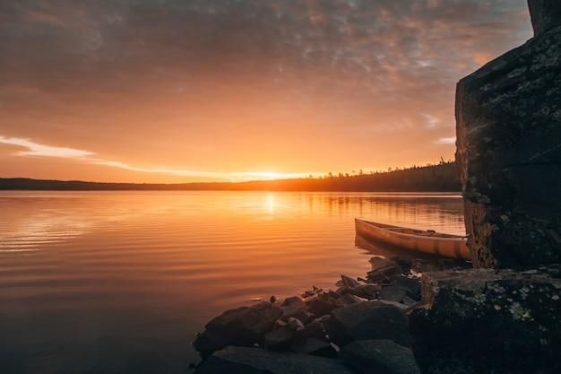 Schöner langer schuss eines kanus auf einem see nahe steinhügeln während des sonnenuntergangs