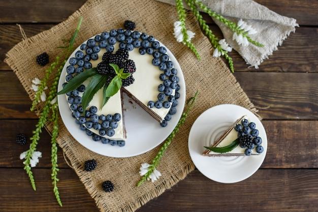 Schöner leckerer kuchen mit weißer sahne und beeren der heidelbeere