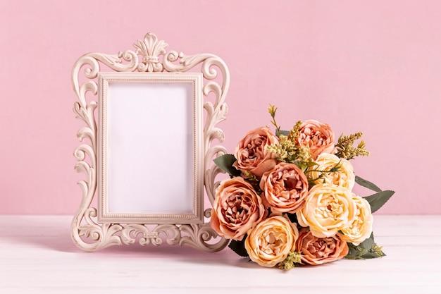 Schöner leerer rahmen mit rosafarbenem blumenstrauß