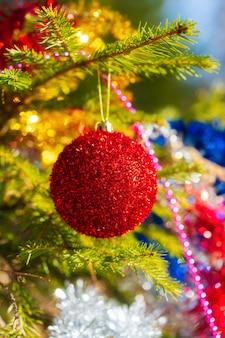 Schöner leuchtender roter weihnachtsball, der am zweig der weihnachtskiefer hängt. selektiver weichzeichner im vordergrund, buntes, verschwommenes bokeh im hintergrund. nahaufnahme der feiertagszusammensetzung für ein glückliches neues jahr.