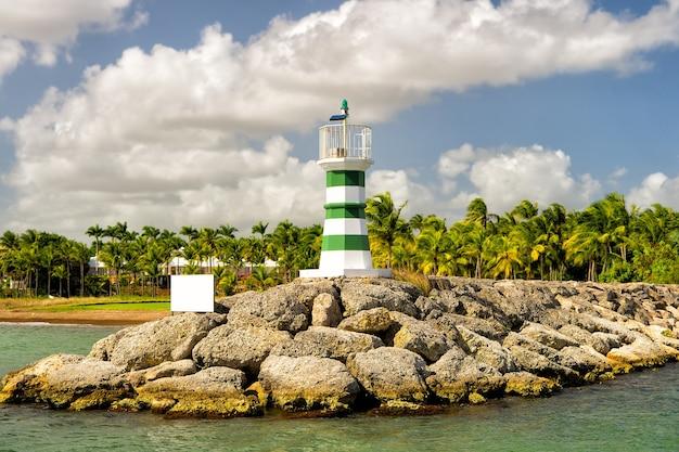 Schöner leuchtturm mit streifen am steinigen hafen in der nähe von wasser sonniger tag im freien mit grünen palmen und bewölktem blauem himmel im sommer