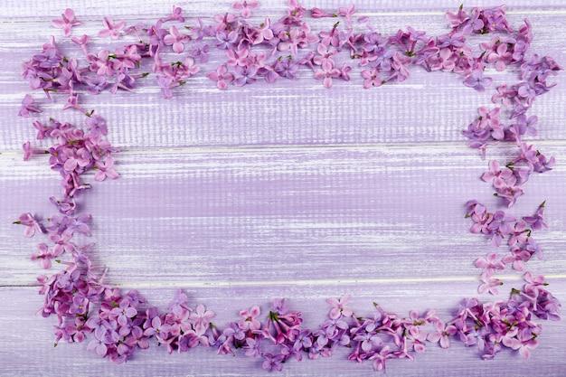 Schöner lila blumenrahmen auf holz