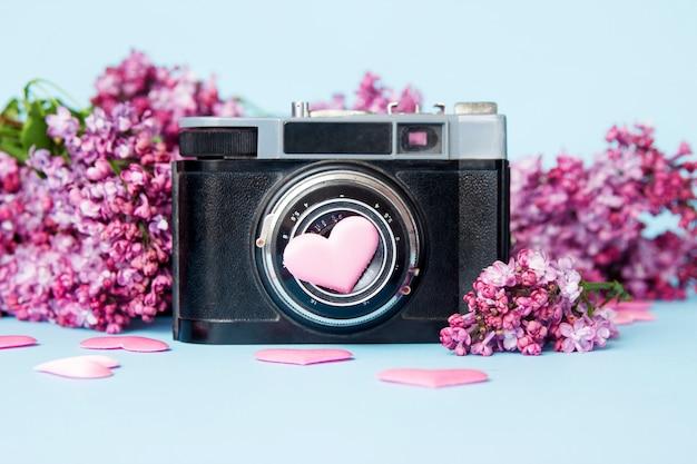 Schöner lila blumenstrauß und retro- fotokamera auf einem blauen hintergrund