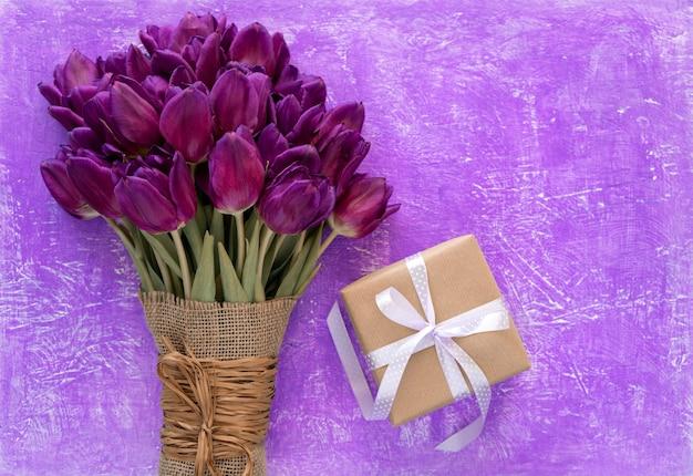Schöner lila tulpenstrauß und geschenkbox auf einem lila tisch.