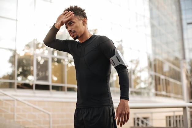 Schöner lockiger dunkelhäutiger mann in schwarzem langärmeligem t-shirt und shorts berührt sein gesicht