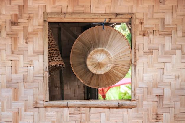 Schöner lokaler handgefertigter asiatischer hut auf der oberfläche des bambus, der am fenster eines bambushauses hängt.