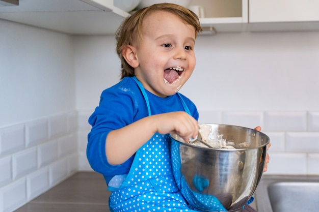 Schöner lustiger blonder kleiner kleinkindjunge, der kuchen und muffins in der häuslichen küche backt
