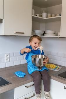 Schöner lustiger kleiner kinderjunge, der kuchen backt und teig in der häuslichen küche schmeckt