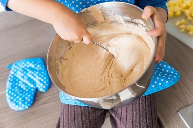 Schöner lustiger kleiner kleinkindjunge, der küchenschürze trägt, die apfel-hauskuchen backt