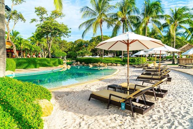 Schöner luxuriöser regenschirm und stuhl um den außenpool im hotel und resort mit kokospalme bei sonnenuntergang oder sonnenaufgang - urlaubs- und urlaubskonzept