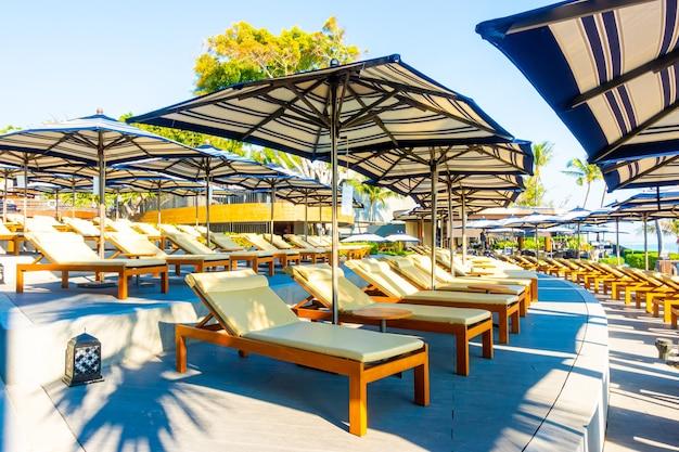 Schöner luxus-sonnenschirm und -stuhl um den außenpool im hotel und resort mit kokospalme für reise- und urlaubskonzept