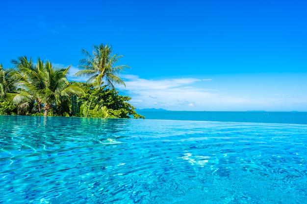 Schöner luxusaußenpool im hotelerholungsort mit seeozean um kokosnusspalme und weiße wolke auf blauem himmel
