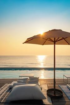 Schöner luxuspool auf seeansicht und regenschirm und stuhl im hotel nehmen zuflucht