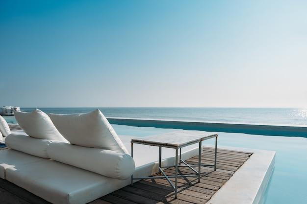 Schöner luxuspool auf seeansicht und strandstuhl im hotel nehmen mit blauem himmel zuflucht