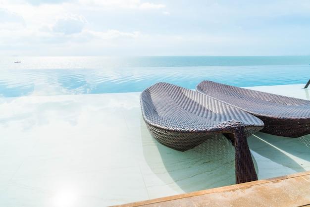 Schöner luxusregenschirm und stuhl um swimmingpool im freien im hotel und in erholungsort