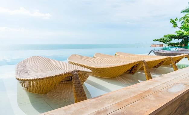 Schöner luxusregenschirm und -stuhl um swimmingpool im hotel und im erholungsort
