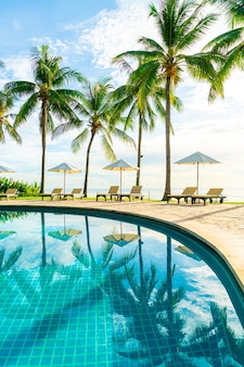 Schöner luxusschirm und stuhl um den außenpool im hotel und resort mit kokospalme bei sonnenuntergang oder sonnenaufgang - urlaubs- und urlaubskonzept