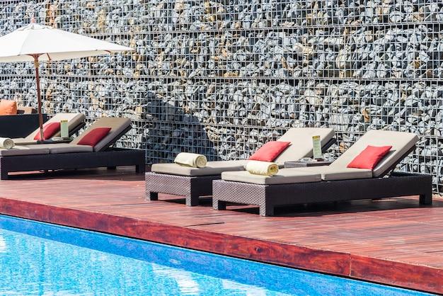 Schöner luxusstuhl mit sonnenschirm-deck und pool-resort