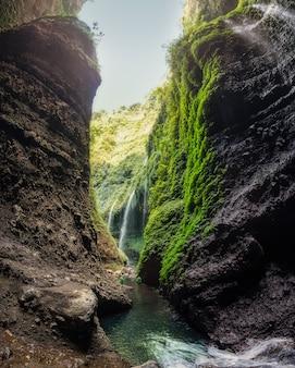 Schöner madakaripura-wasserfall im felsigen tal