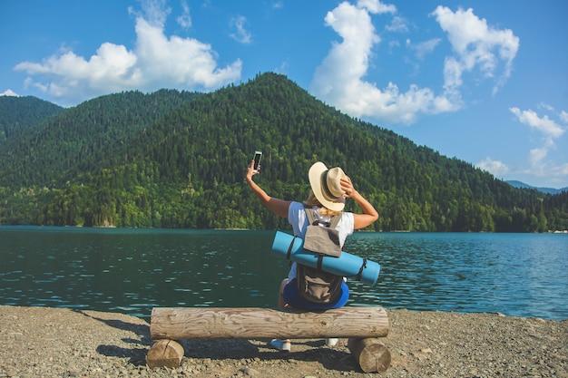 Schöner mädchen-reisender macht fotos von einem großen blauen gebirgssee im hintergrund der berge