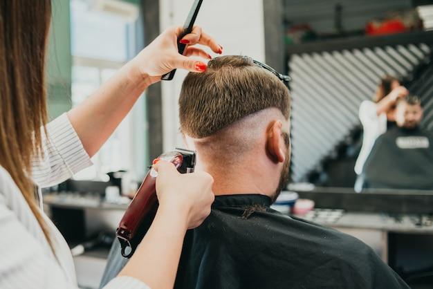 Schöner mädchenfriseur schneidet einen bärtigen mann im salon