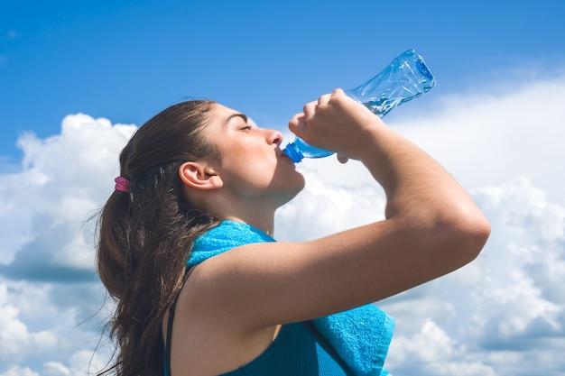 Schöner mädchenläufer hat pause, trinkwasser gegen klaren blauen himmel trinkend.