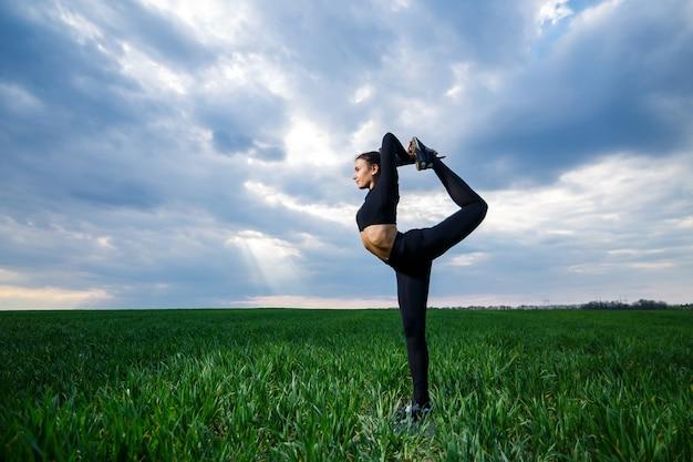 Schöner mädchenturner auf dem grünen gras macht yoga. eine schöne junge frau auf einem grünen rasen führt akrobatische elemente durch. flexible turnerin in schwarz macht einen handstand im split