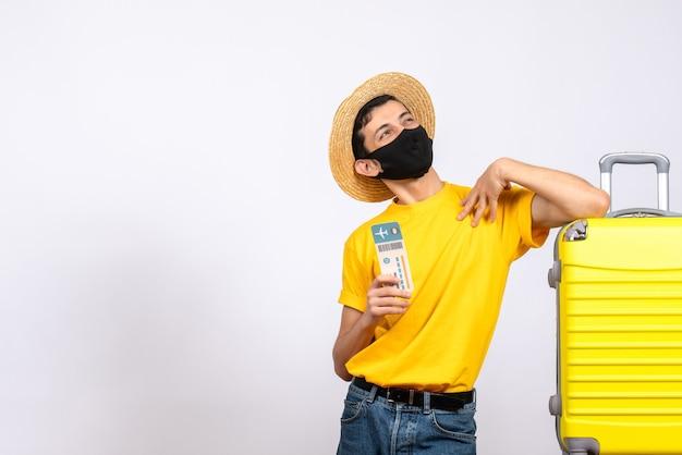 Schöner männlicher tourist der vorderansicht mit strohhut, der nahe gelbem koffer hält, der reiseticket hält