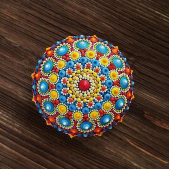 Schöner mandala-felsen auf holzhintergrund
