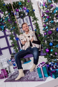Schöner mann, der auf einer terrasse nahe bei einer weihnachtsdekoration sitzt