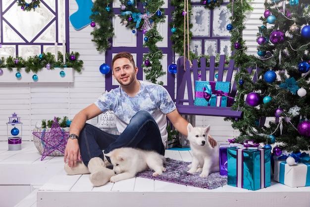Schöner mann, der auf einer terrasse nahe bei weihnachten sitzt