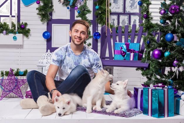 Schöner mann, der auf terrasse nahe bei weihnachten sitzt