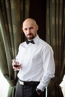 Schöner mann, der cognac im restaurant trinkt.