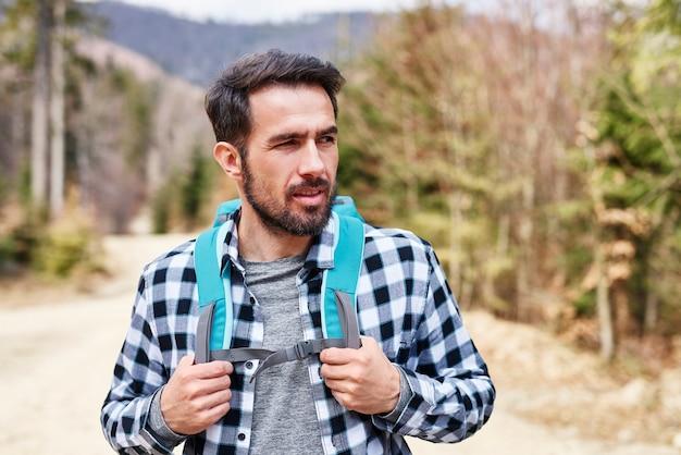 Schöner mann, der die aussicht während der reise in den bergen genießt