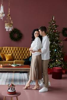 Schöner mann, der eine schöne langhaarige frau umarmt, während er im weihnachtlich dekorierten innenraum posiert