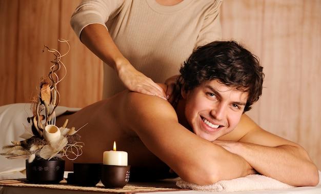 Schöner mann, der entspannungsmassage im spa-salon bekommt