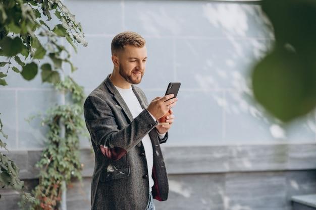 Schöner mann, der kaffee trinkt und telefon benutzt