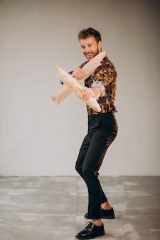 Schöner mann, der mit französischen baguettes steht standing