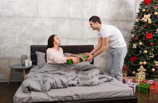 Schöner mann, der seiner glücklichen freundin ein geschenk gibt, während sie in einem bett sitzt und einen schlafanzug im schlafzimmer im loft-stil mit weihnachtsbaum mit vielen geschenken trägt