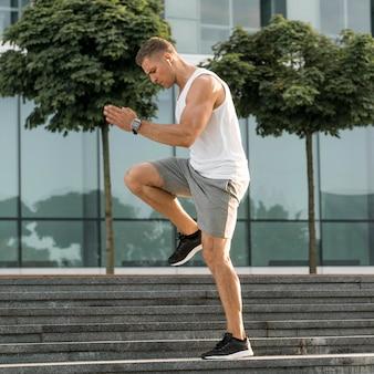 Schöner mann der seitenansicht, der draußen trainiert