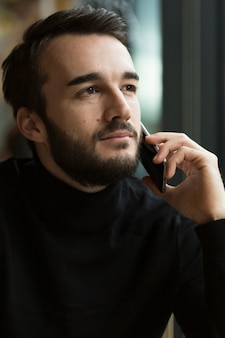 Schöner mann der vorderansicht, der über telefon spricht
