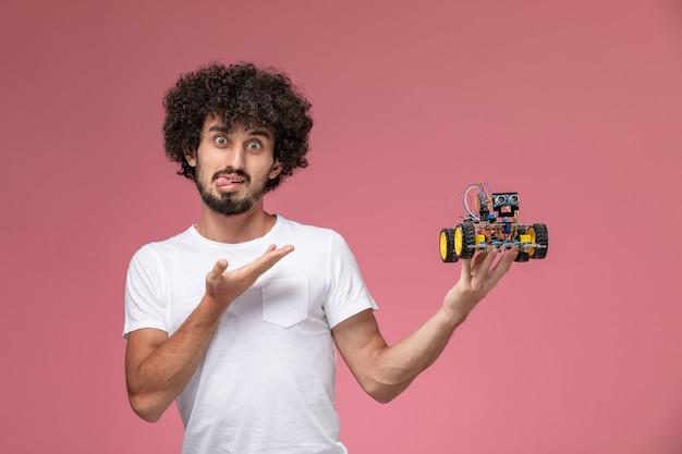 Schöner mann der vorderansicht, der verrücktes gesicht mit roboterinnovation macht