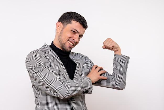 Schöner mann der vorderansicht im anzug, der armmuskel auf weißem hintergrund stehend zeigt