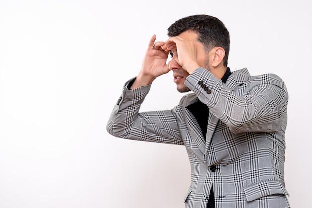Schöner mann der vorderansicht im anzug, der handferngläser macht, die auf weißem lokalisiertem hintergrund stehen