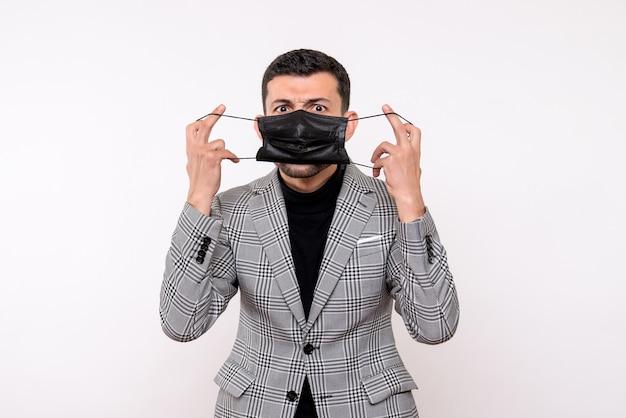 Schöner mann der vorderansicht im anzug, der maske auf weißem lokalisiertem hintergrund setzt