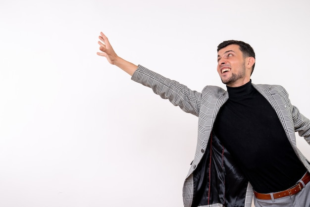 Schöner mann der vorderansicht im anzug, der versucht, etwas zu fangen, das auf weißem hintergrund steht