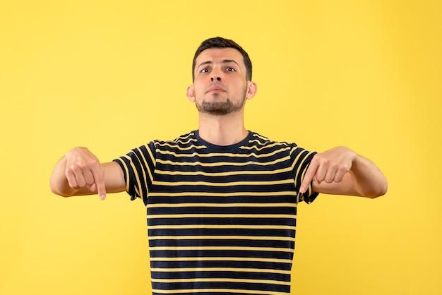 Schöner mann der vorderansicht im gestreiften schwarzweiss-t-shirt, das auf den gelben isolierten hintergrund des bodens zeigt