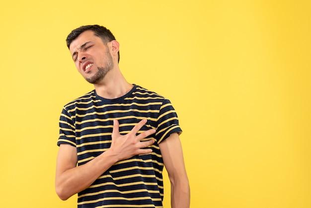 Schöner mann der vorderansicht im gestreiften schwarzweiss-t-shirt, das brust auf gelbem lokalisiertem hintergrund hält