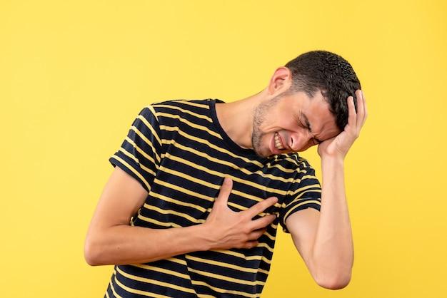 Schöner mann der vorderansicht im gestreiften schwarzweiss-t-shirt, das kopf und brust auf gelbem lokalisiertem hintergrund hält